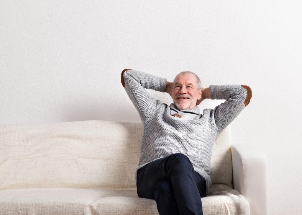 Glücklicher Senior (Peter) entspannt sich auf Wohnzimmerbank.