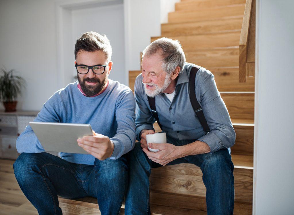 Vater und Sohn (Peter und Gerhard) bestellen am Tablet eine JAMES Notrufuhr.