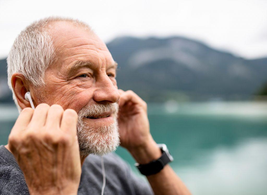 Sportlicher Senior (Peter) beim Wandern mit Kopfhörern und der JAMES Notrufuhr B6.