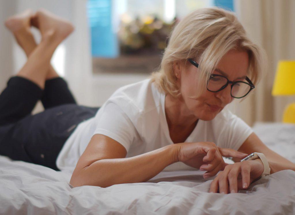 Seniorin spielt mit der weißen Notrufuhr B6 am Bett.