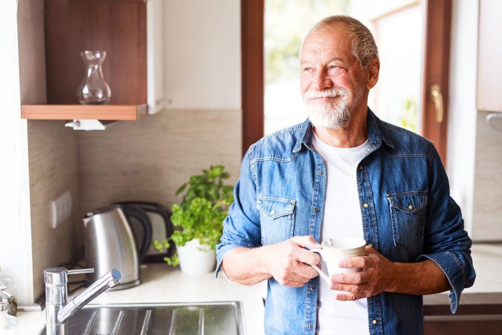 Glücklicher Senior (Peter) steht mit Kaffeetasse in der Küche und blickt verträumt aus dem Fenster.