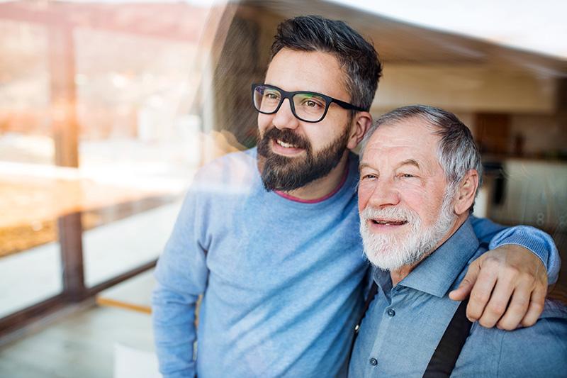 Ein älterer Vater (Peter) und Sohn (Gerhard) genießen die Softwarelösungen von ilogs healthcare.