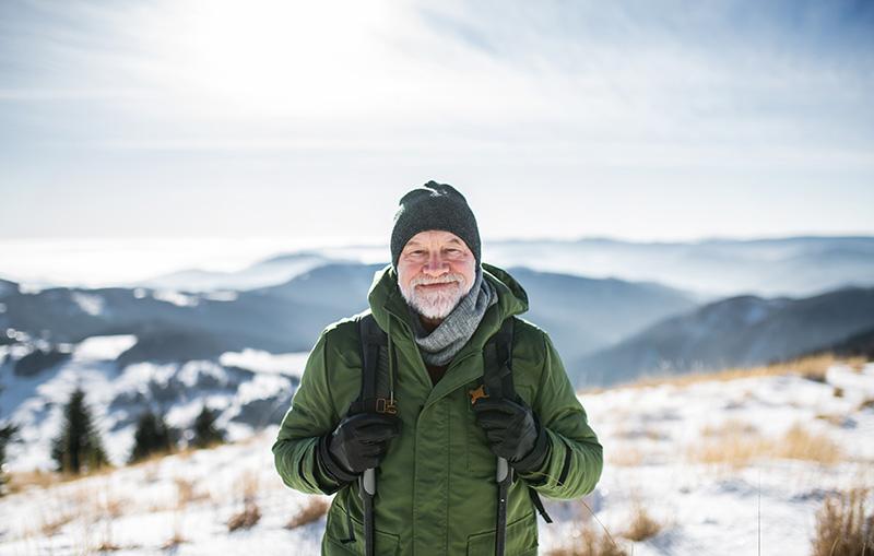 Senior (Peter) mit Rucksack auf Wanderschaft in schneebedeckter Berglandschaft.