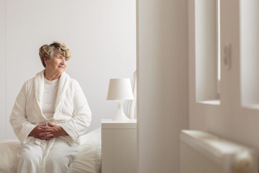 Seniorin (Maria) sitzt auf Bett und blickt sehnsüchtig aus dem Fenster.