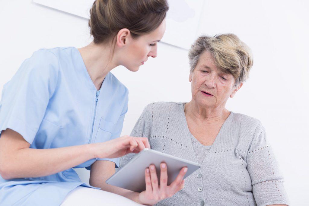 Seniorin (Maria) bekommt das JAMES Tablet von einer Pflegekraft (Anna) erklärt.