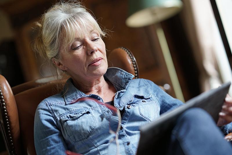Seniorin (Elfriede) sitzt im Wohnzimmer und bedient aufmerksam das JAMES Tablet.