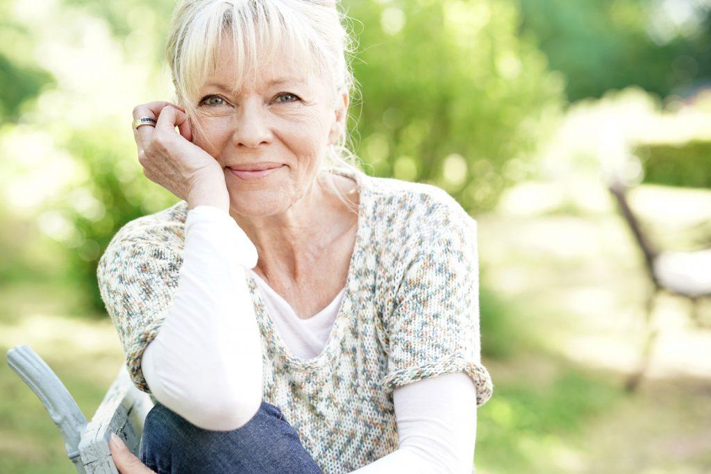 Glückliche Seniorin (Elfriede) in der Natur, dank Hausnotrufsystem JAMES.