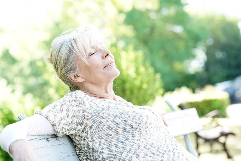 Seniorin (Elfriede) entspannt sich auf Holzbank in der Natur.