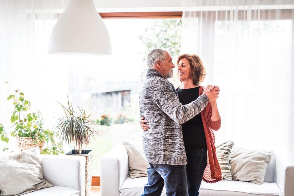 Glückliches Seniorenpaar (Peter und Susanne) tanzt im Wohnzimmer