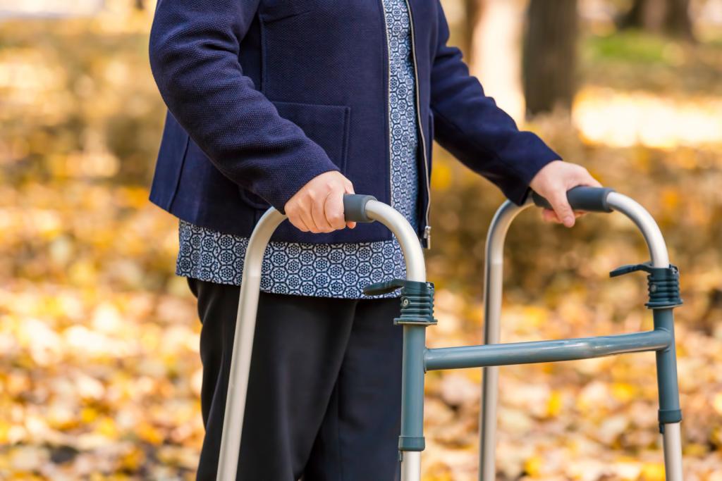 Alte Frau mit Gehhilfe vor Herbstblätterkulisse.