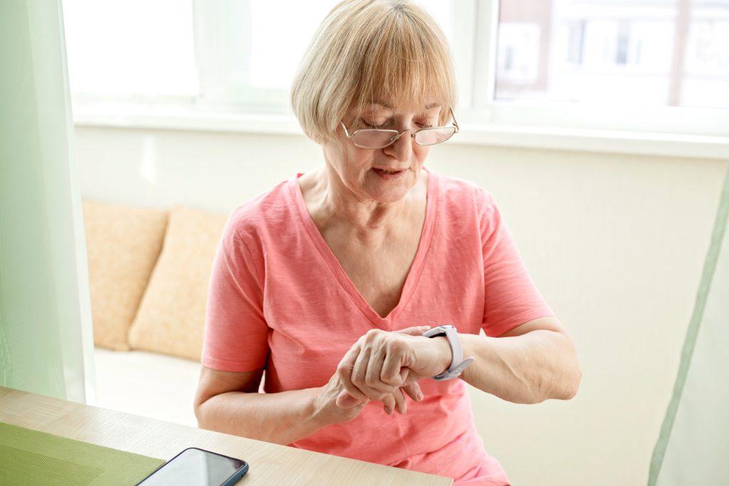 Seniorin bedient die JAMES Notrufuhr B6 im Wohnzimmer.