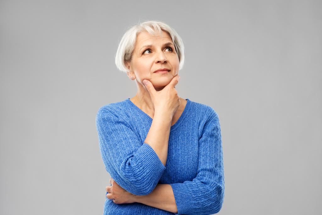 Nachdenke Seniorin in blauem Pullover braucht Hilfe beim Einrichten ihres JAMES Produkts.