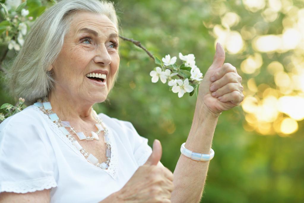 Glückliche alte Frau im Garten zeigt Daumen nach oben.