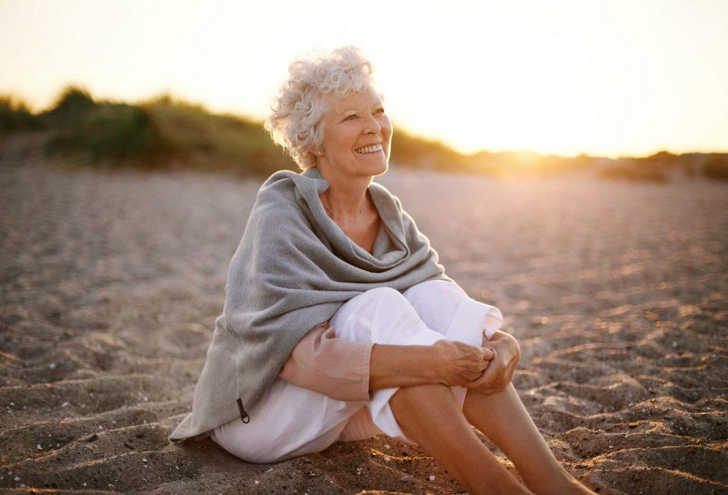 Ältere Frau sitzt am Strand und genießt den Sonnenuntergang