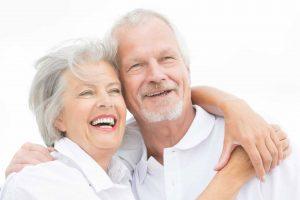 Glückliches Seniorenpaar in Umarmung auf weißem Hintergund